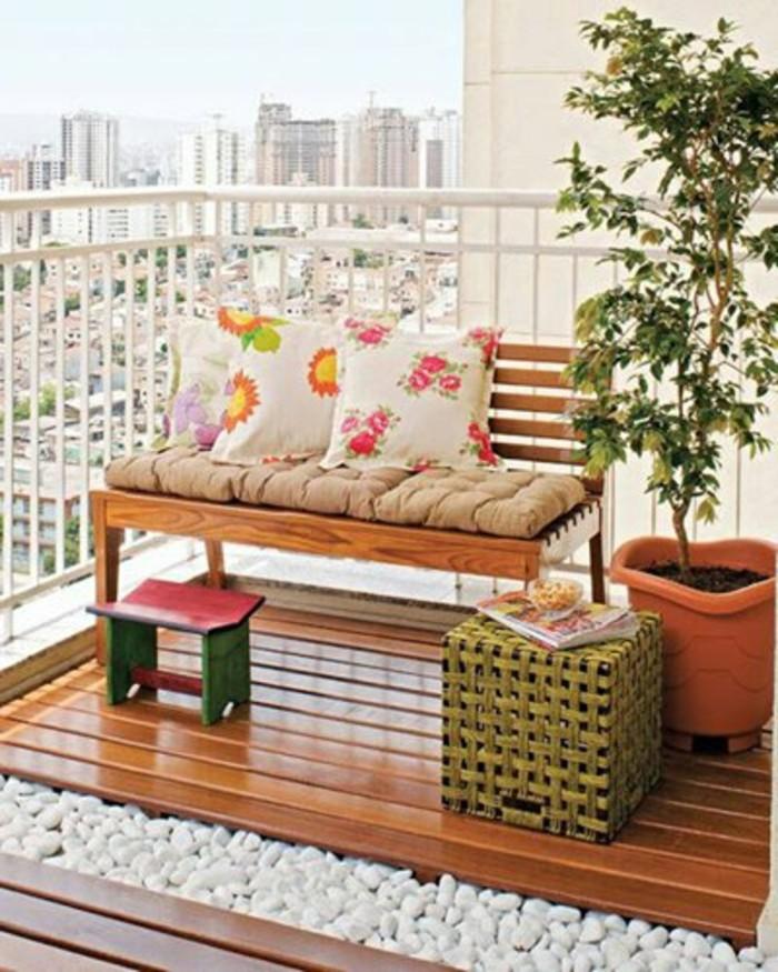 terrasse en bois et chemin de galets avec un banc en bois, petite table basse cube et plante dans un grand pot