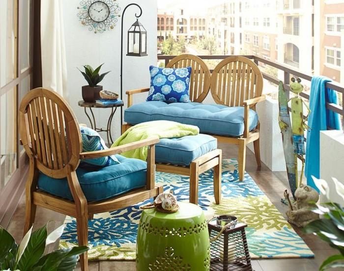 chaise et canapé en bois avec des coussins d assise bleus, tapis à motifs fleuris, revetement carrelage aspect bois, ambiance exotique amenagement balcon