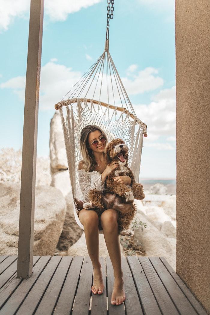 Femme et son chien dans un chaise hamac, tenue style hippie chic robe bohème chic dentelle, robe hippie chic