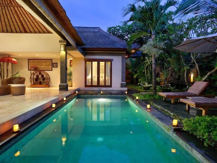 Maison luxueuse avec belle piscine individuelle, chaise longues et palmiers