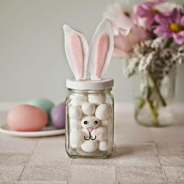 bocal en verre avec oeufs, oreilles de lapin au top, assiettes d'oeufs téintés, décoration oeuf de paques