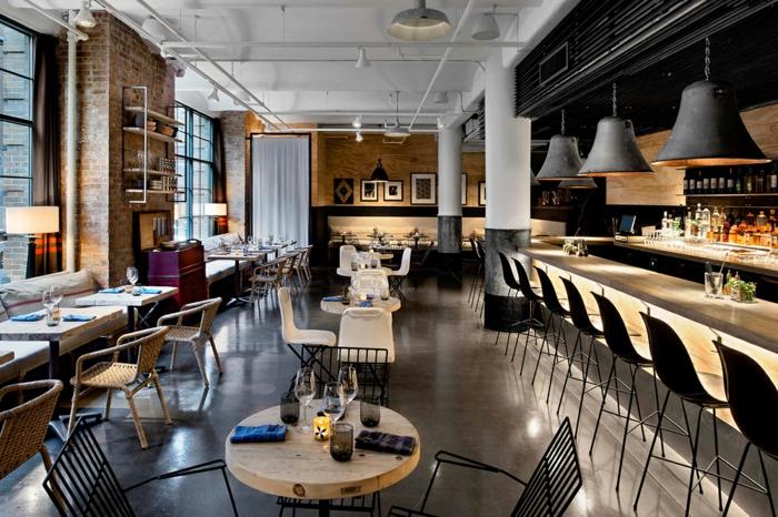 joli café en style loft industriel, lampes suspendues, petites tables carrées, plafond blanc, chaises de bar noires