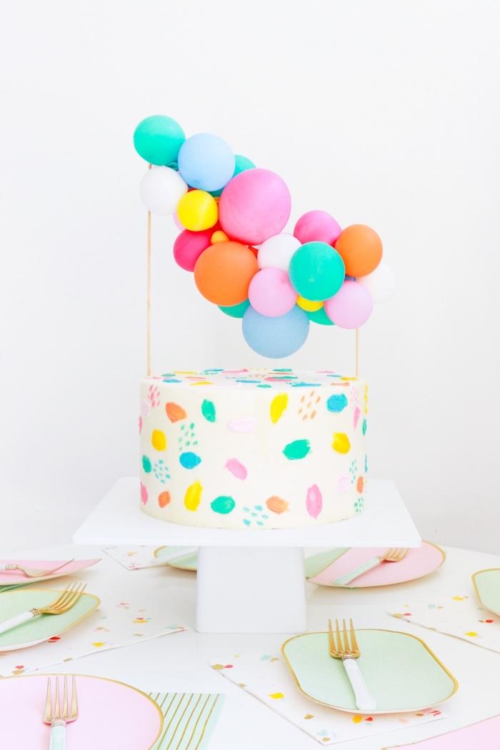 gateau anniversaire dessin aquarelle réalisé avec du glaçage coloré, orné d'un cake topper de mini-ballons