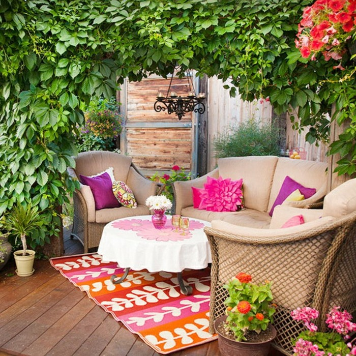 exemple de decoration balcon fleuri avec canapé et fauteuils marron, table basse décorée à motifs fleuris, tapis multicolore, arche de végétation verte
