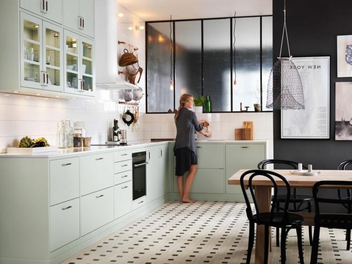 sol carrelage damier, table en bois clair, chaises noires, verrière d'artiste, placards suspendus, tableau deco cuisine