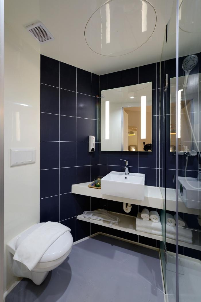 petite salle de bains qui combine une revêtement mural en pvc à finition brillante et des carreaux grands formats en bleu foncé