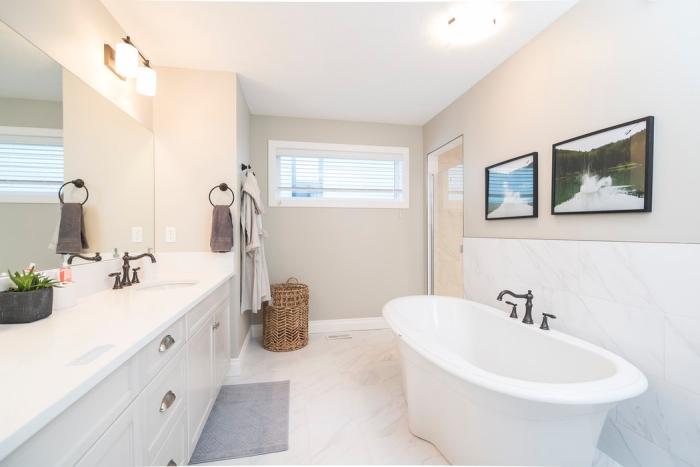 carrelage de salle de bain imitation marbre posé au sol et à la mi-hauteur du mur derrière la baignoire îlot