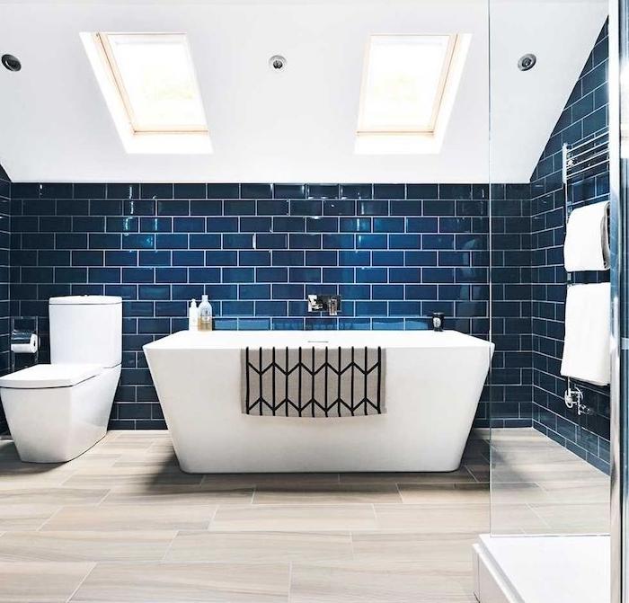 carrelage bleu nuit dans une salle de bain en blanc et bleu, baignoire et wc blanc, carrelage imitation parquet, douche avec paroi vitré