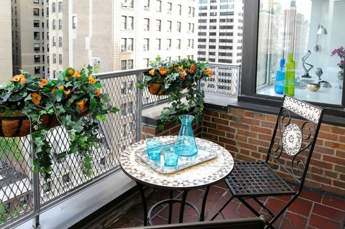 table pour balcon avec plateau en mosaique, chaise metallique noire, garde corps fleuri à pots fleurs, revetement en carreaux de grès cérame