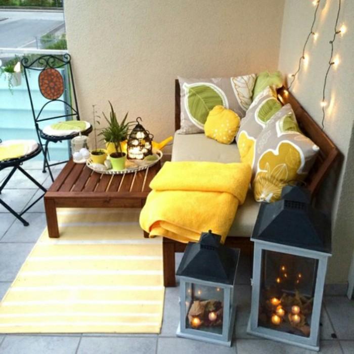 idée de table et canapé bois marron avec deco de coussin d assise grise et coussins decoratifs gris, jaune et vert, tapis jaune, lanternes decoratives