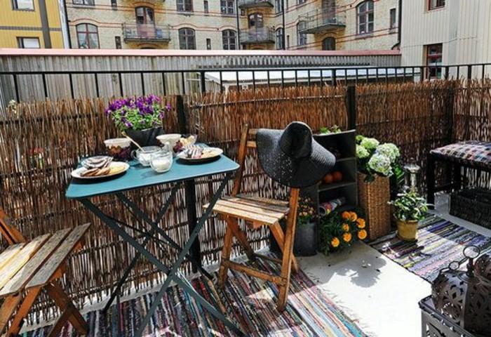 exemple amenagement petite terrasse avec brise vue vegetale, chaises de bois pliantes, table pliante metallique, plusieurs plantes fleuries