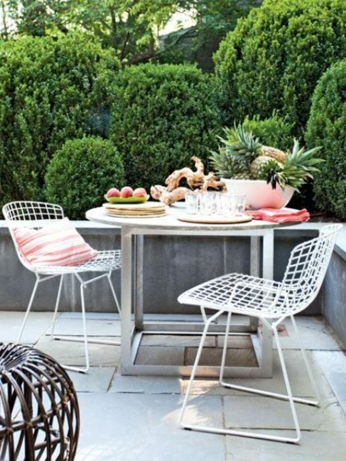 table metallique et chaises blanches metalliques dans une terrasse en beton avec vue sur un jardin végétalisé, terrasse design