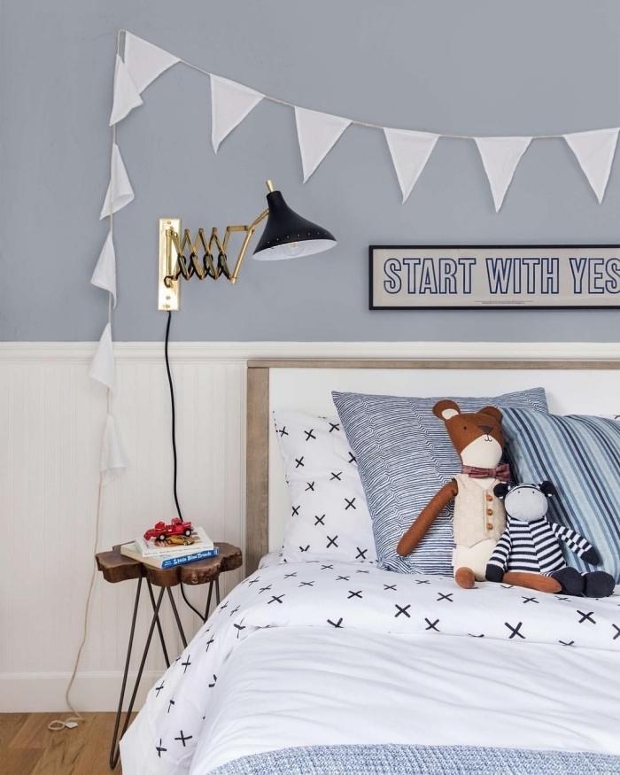 lambris blanc en tête de lit dans la chambre d'enfant en contraste léger avec le mur bleu gris, habiller un mur avec du lambris posé à la mi-hauteur