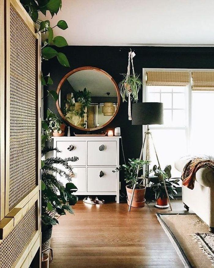 Intérieur moderne dans une pièce avec beaucoup de plantes vertes, miroir ronde, lampe à trois pieds, canapé beige, tapis persienne, salle de sejour murs bleu fonce