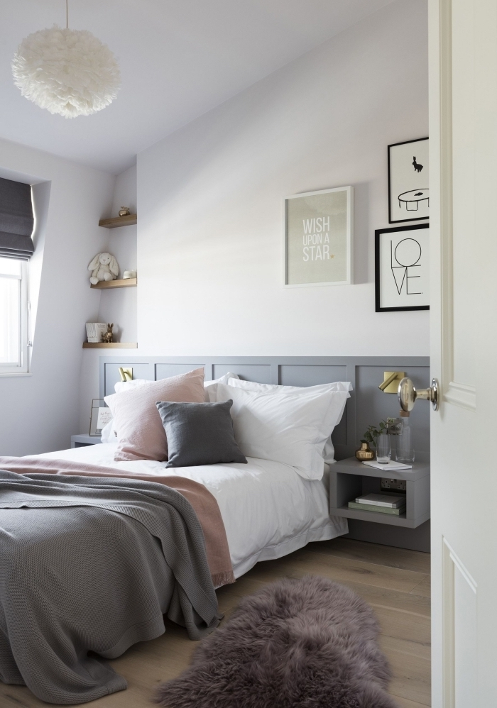 un soubassement bois peint en gris qui fait office de tête de lit avec des tables de nuit intégrées dans une chambre à coucher style scandinave