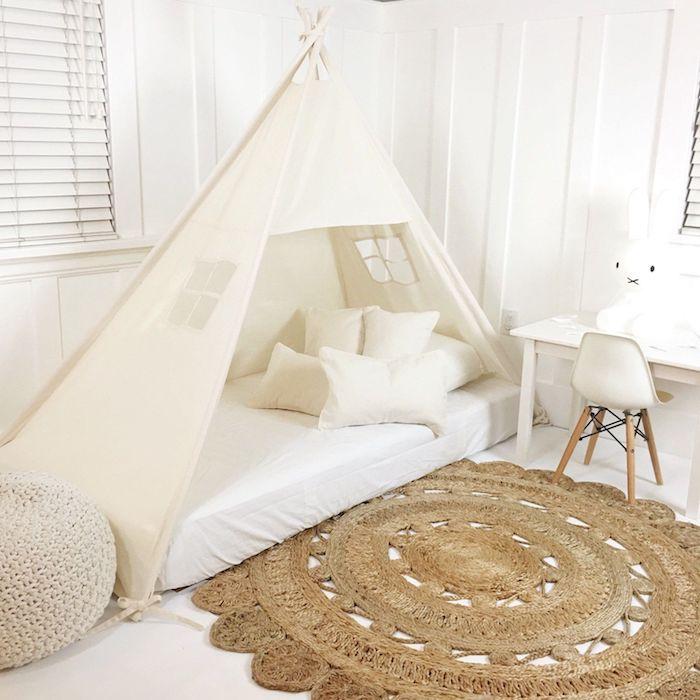 lit et tipi enfant deux en un, tapis tressé rond sur un sol blanc, bureau et chaise scandinave, murs blancs, pouf tricoté