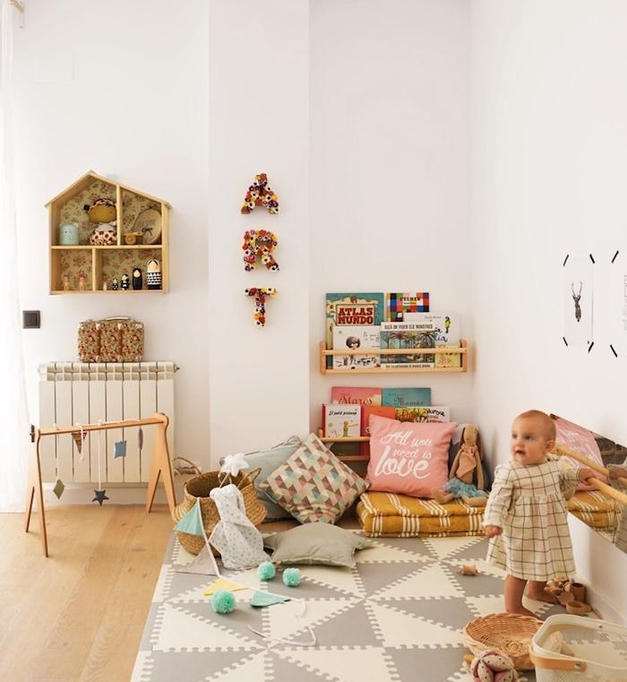 matelas jaune sur tapis gris et blanc, coussins décoratifs etageres basses bois pour livres, mobile montessori tapis d'éveil