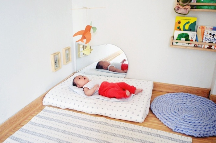 matelas bébé au sol sur parquet bois et tapis gris et blanc, tapis d'éveil montessori tricoté, murs blancs, miroir sur l horizontal, etagere bibliothèque livres enfant