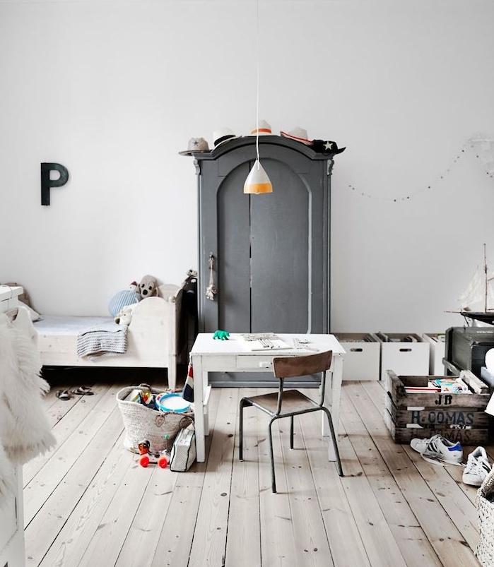 rangement cagette de bois pour jouets, armoire grise, lit blanc bas, parquet bois aspect usé, bureau et chaise bois et metal, murs blancs, decoratio chambre mixte style scandinave