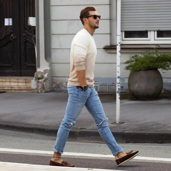style vestimentaire homme casual chic, paire de jeans clairs et déchirés avec blouse beige assortis avec chaussures et bracelet en marron