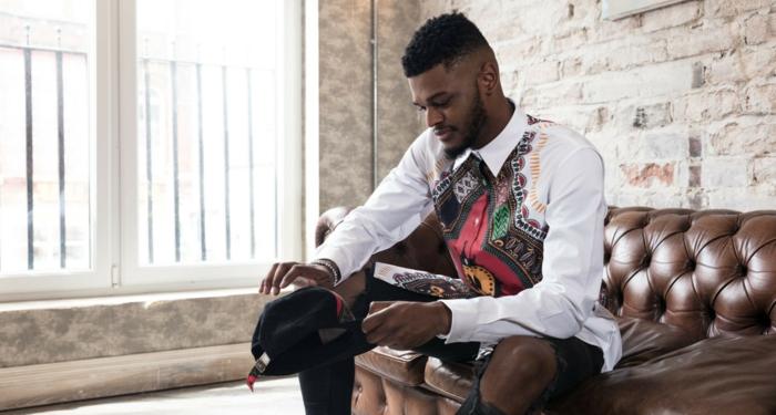 tenue africaine homme, chemise chic aux imprimés colorés, coupe homme dégradé, sofa en cuir, short et chaussettes longues