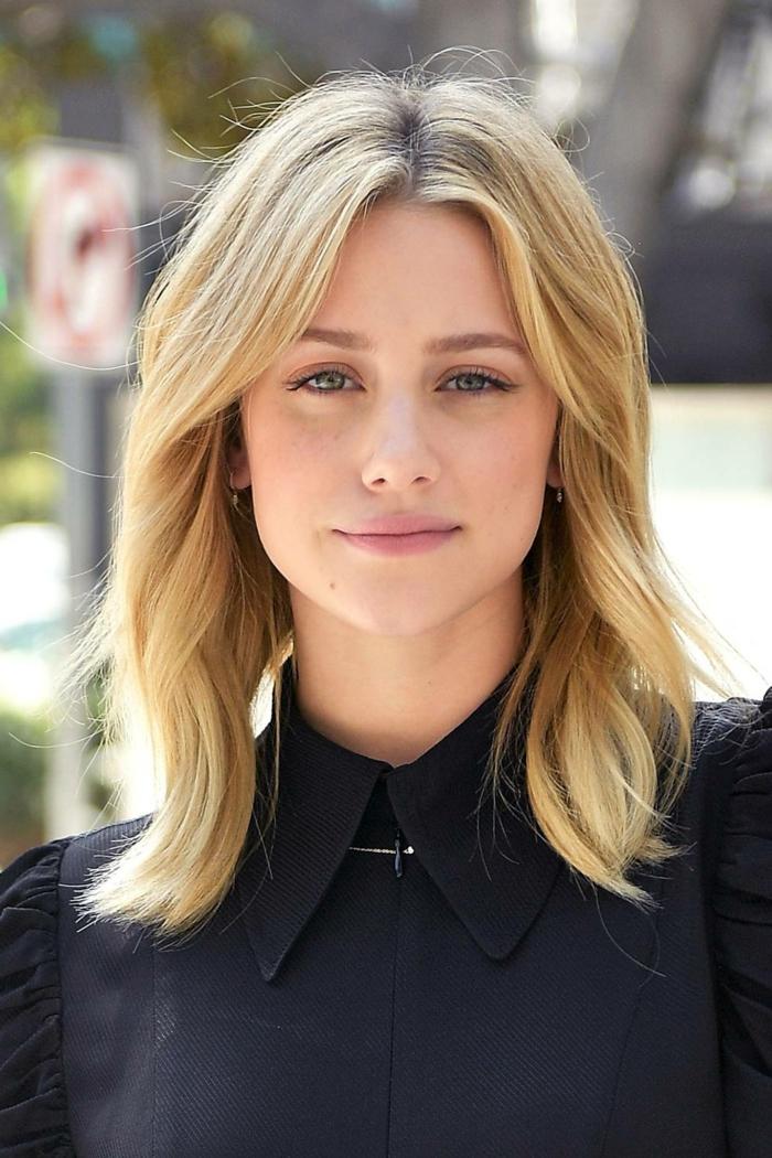 cheveux longs, couleur blonde, chemise noire, maquillage discret, frange séparée en deux efffilée