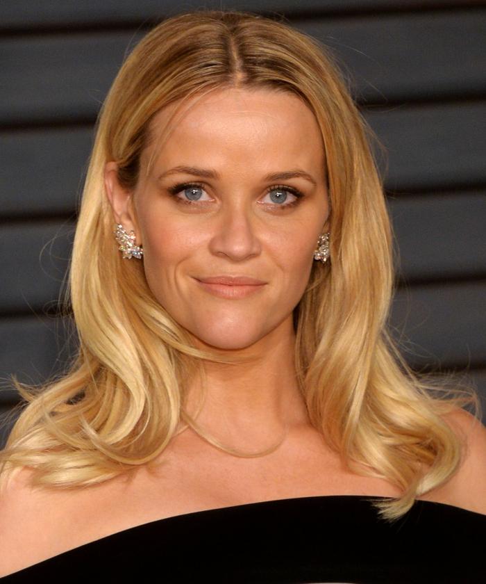 la coiffure de Reese Witherspoon, cheveux blonds, yeux bleus, boulces d'oreille, robe élégante noire