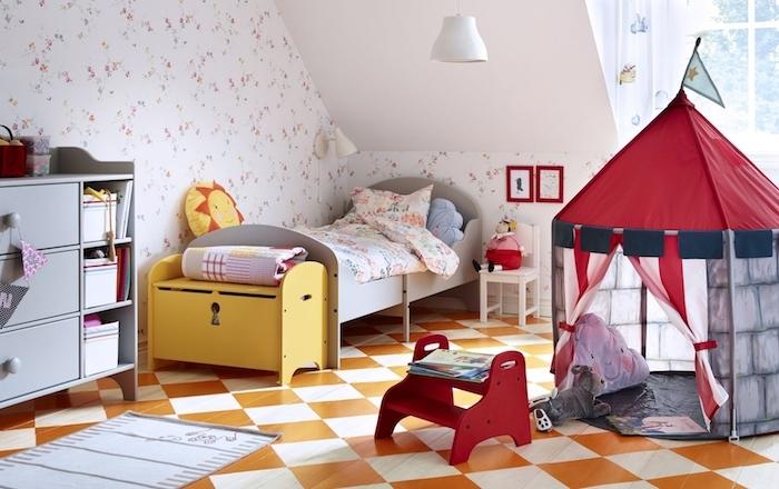 chambre sous pente enfant avec lit bas, meuble commode à rangements ouverts bas, sil carrelage orange et blanc, tipi enfant maisonette, papier peint motifs floraux