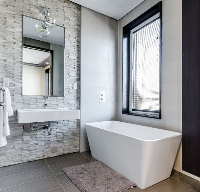 une ambiance relaxante dans une salle de bains qui combine trois types de carreaux dans les tons gris, carrelage en mosaïque posé en crédence derrière le plan vasque