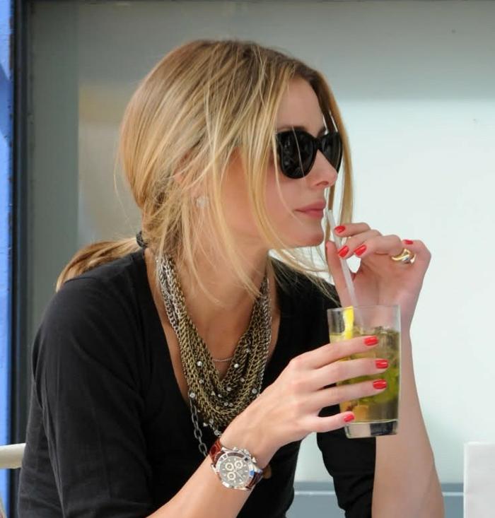 pull noir, lunettes de soleil, montre à poignet mécanique, colliers accumulés, vernis à ongles rouge