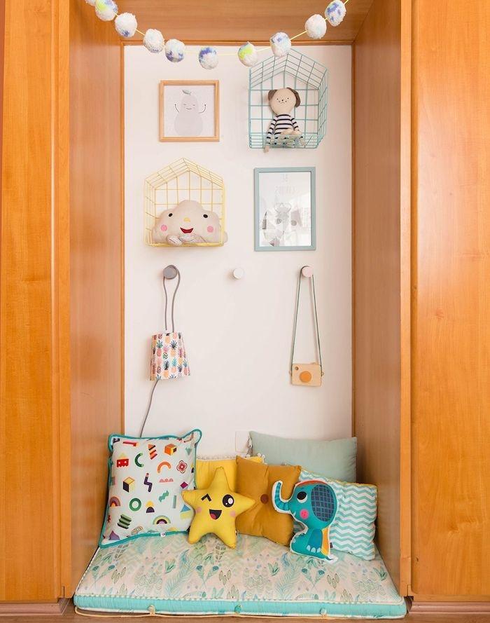 niche murale comme coin activité montessori ou coin lecture enfant avec matelas au sol, multitude de coussins enfant, deco murale enfantine
