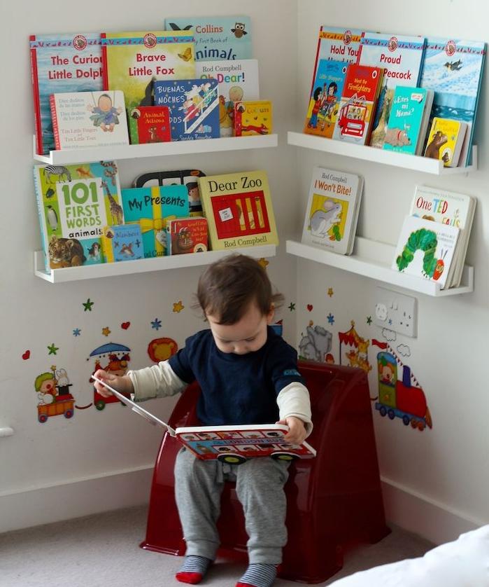 coin lecture montessori jeux avec petit fauteuil enfant et livres rangés sur etagres basses, deco sticker chambre enfant