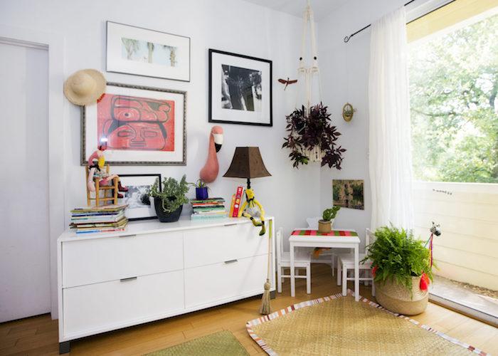petit coin montessori dans le salon, meuble rangement blanc à tiroirs, deco murale artistique, table basse et chaises enfant avec plantes autour