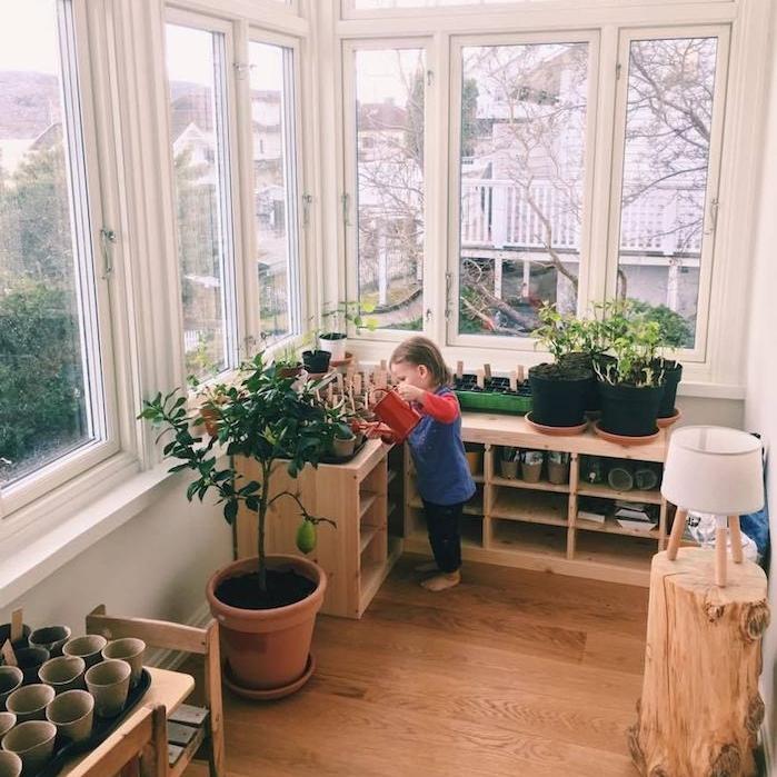 coin vert enfant sur la terrasse couverte, méthode montessori à la maison, apprendre à l enfant à jardiner et s'occuper des plantes, photo enfant en train d arroser plantes