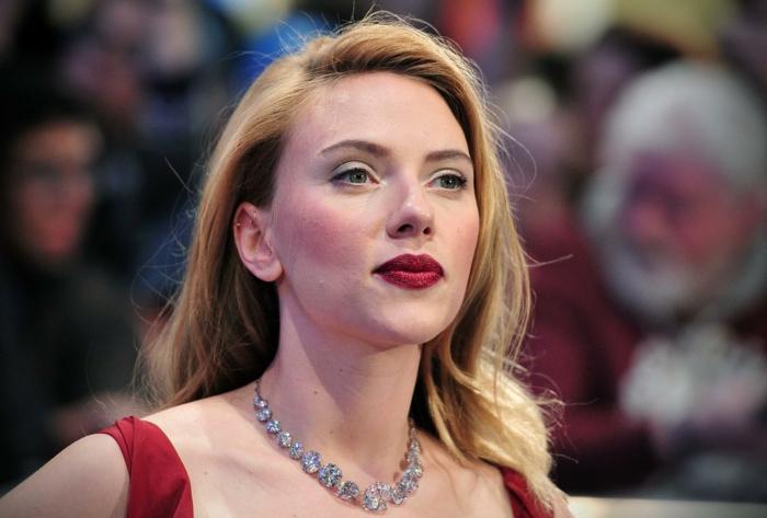 Scarlett Jonasson avec un blond californien, collier pierres précieuses, robe rouge, ombres à paupières bleues