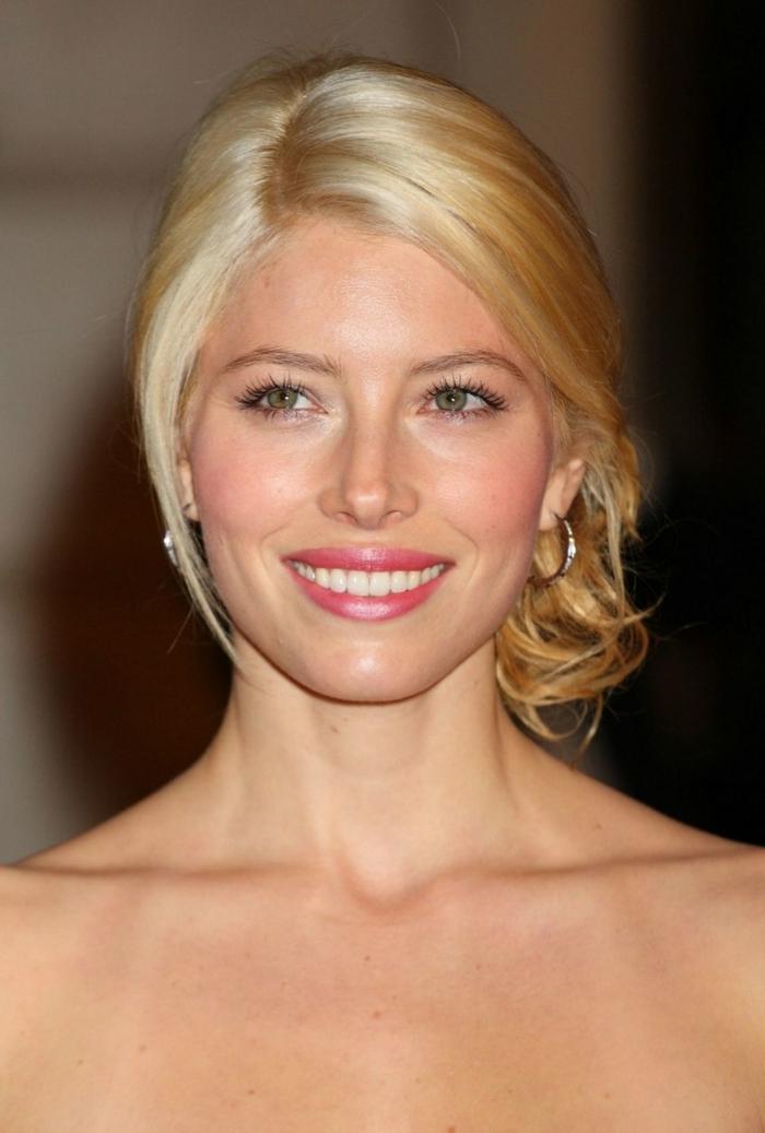 coloration blonde femme, couleur doré des cheveux, yeux bleus, lèvres roses, chignon sur le côté