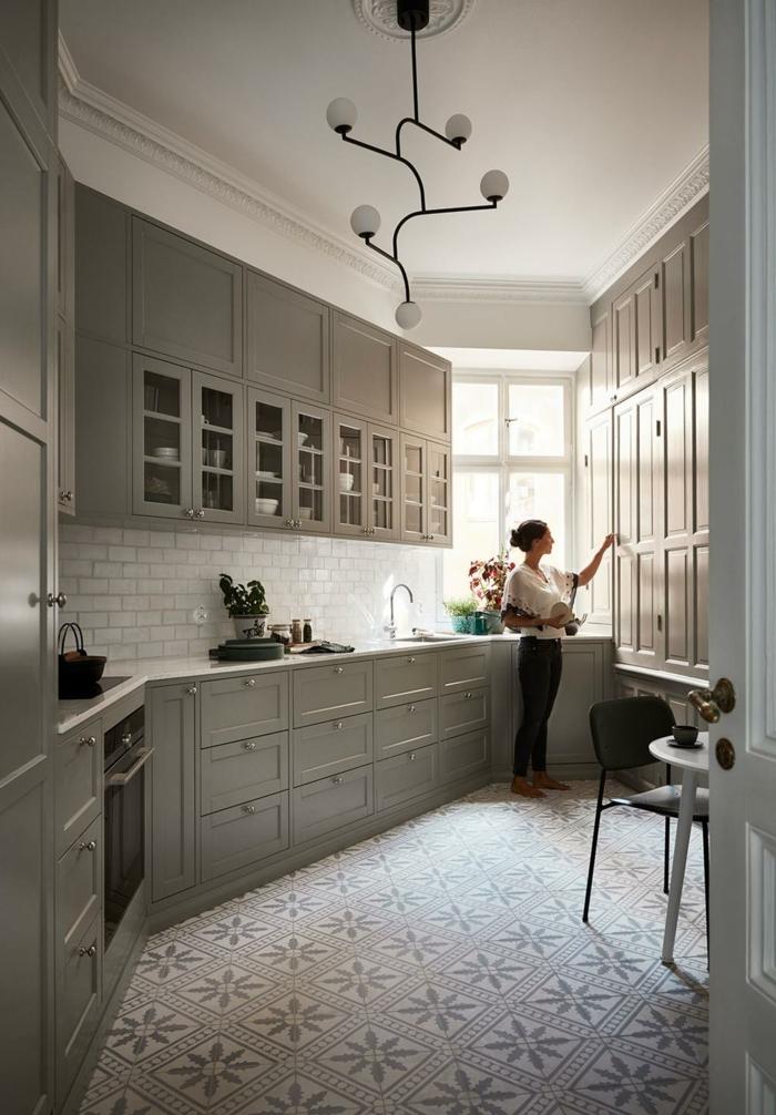 cuisine blanche et grise, armoires de cuisines suspendues grises, petite table blanche et chaise noire