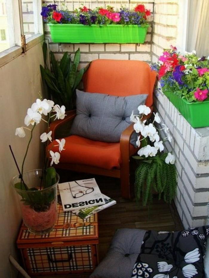 fauteuil de balcon en bois avec un coussin d assise orange et coussin decoratif gris, revetement terrasse bois, petite table coffre, bacs fleuris de fleurs colorées