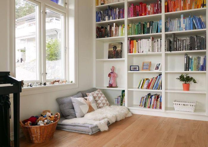 coin lecture enfant dans le salon constitué de matelas gris décoré de coussins, panier à jouets, livres enfant sur les basses etagres d une grande bibliothèque