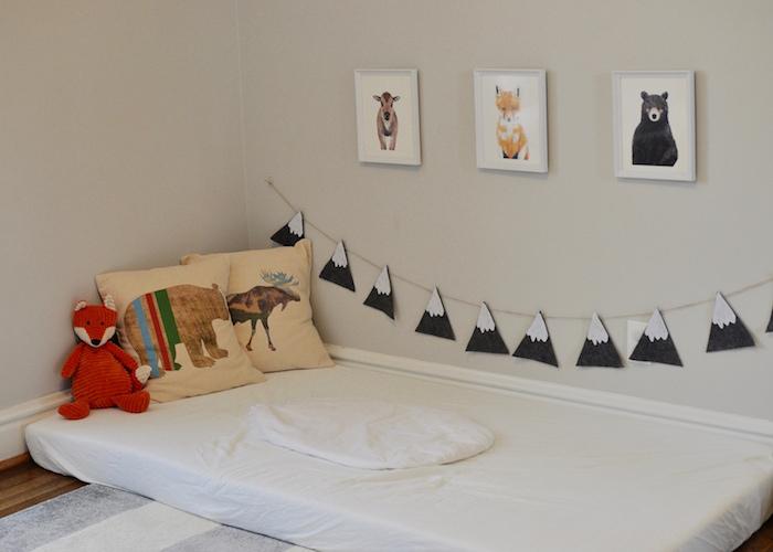 comment amenager un lit au sol, matelas blanc, coussins à motif animal, mur décoré de cadres avec dessins animaux, guirlande motif montagne, jouet renard