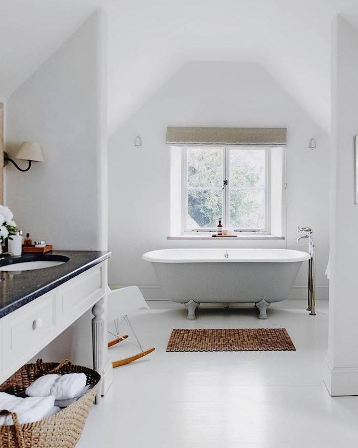 amenagement sous pente, baignoire grise dans une salle de bain blanche, tapis beige, chaise à bascule scandinave, meuble lavabo blanc avec plan de travail granite