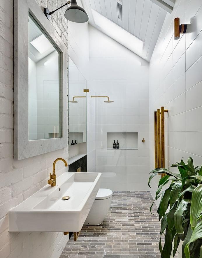 agencement salle de bain sous en pente en longueur, carrelage gris, lavabo blanc à robinetterie laiton, carrelage mural metro blanc