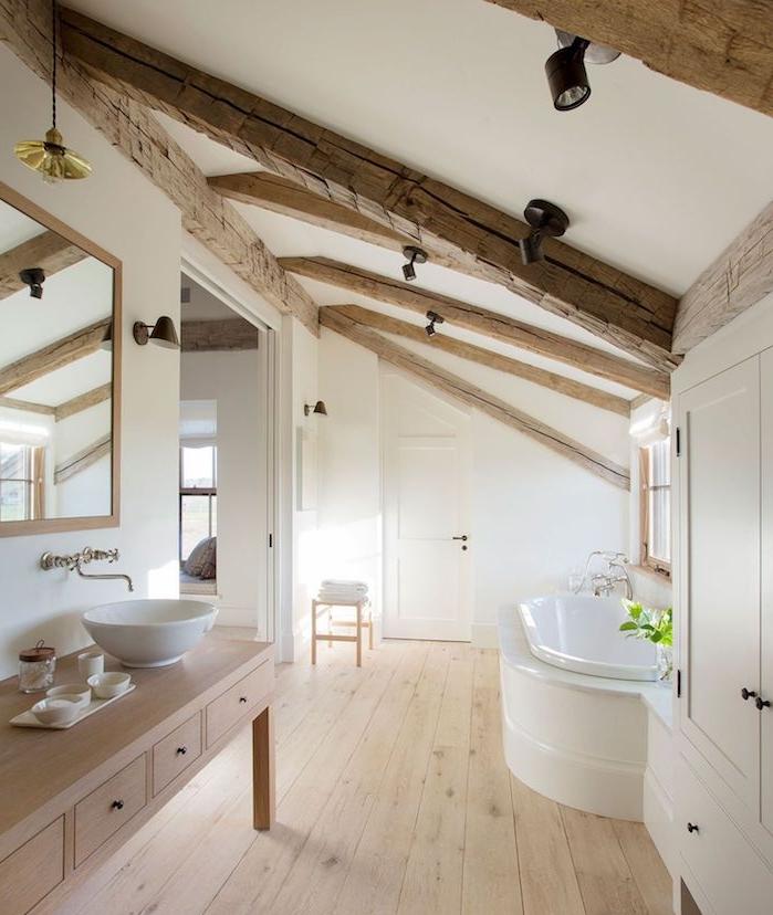 poutres apparentes dans une salle de bain bois et blanc avec baignoire blanche, mobilier et parquet bois, vasque à poser