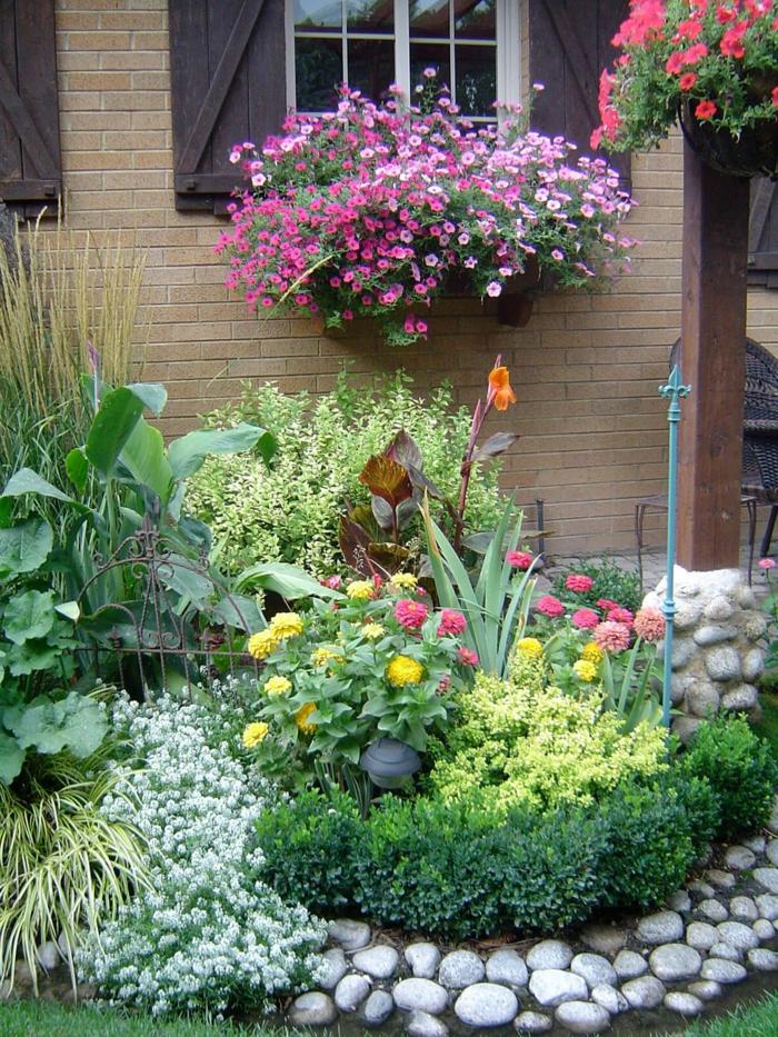 petit massif de fleurs encadré de galets blancs, pots de fleurs suspendus aux fenêtres