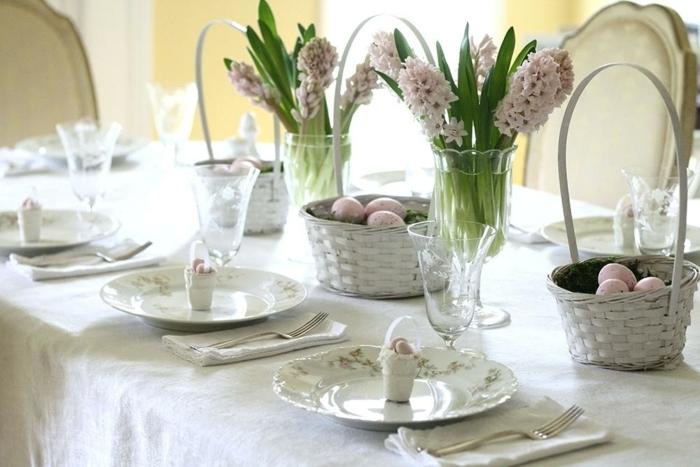 déco de table avec paniers peints blancs, jacinthes mauves, nappe de table blanche, assiettes blanches