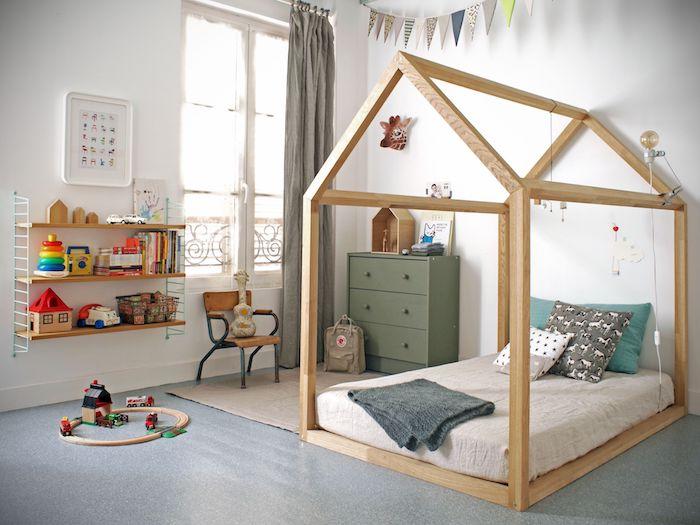 idée de lit cabane montessori en bois avec matelas gris, commode vert olive, tapis beige, sol gris, etagre basse, guirlande fanions