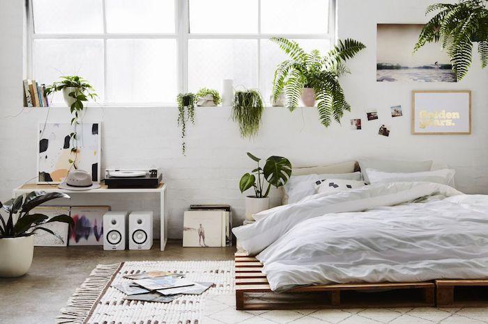 Lit en palettes dans une chambre déco nordique tout blanche avec beaucoup de plantes vertes et des plaques vinyles