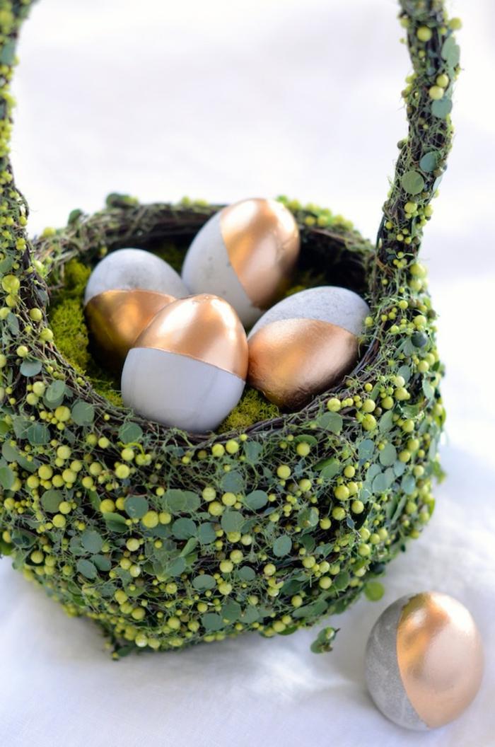décoration de paques à faire avec des oeufs en béton et teinté de peinture cuivrée, grande corbeille verte