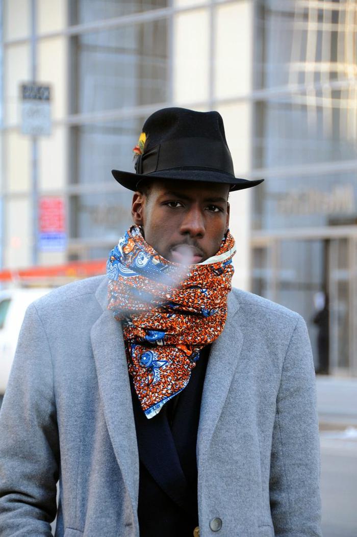 écharpe bariolée aux motifs bleus et oranges, veste gris clair, chapeau cylindre, vetement africain homme
