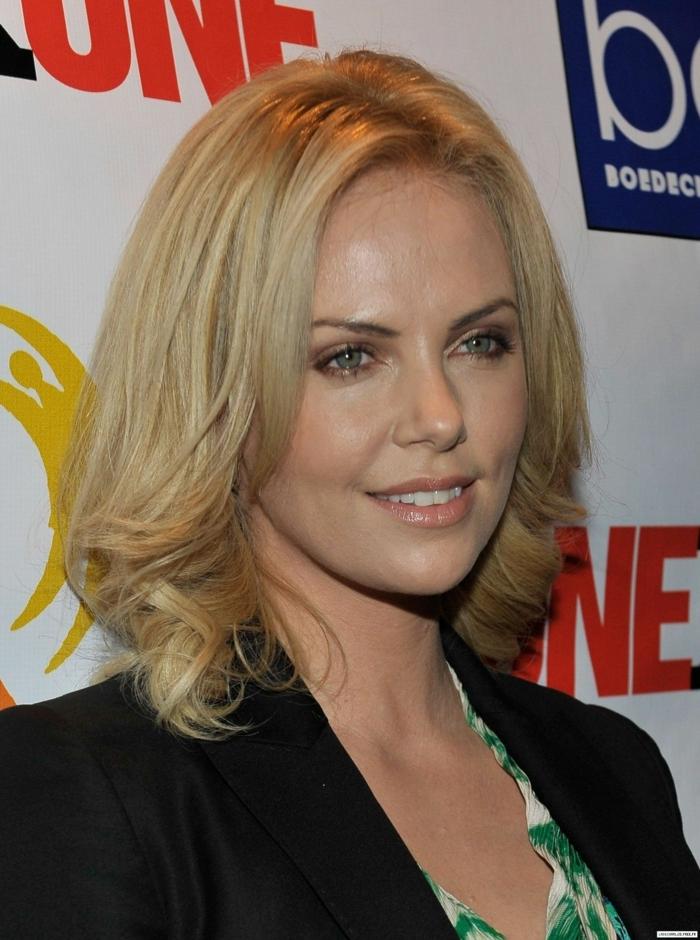 couleur blonde des cheveux, coupe carré légèrement bouclé, yeux bleus, veste noire